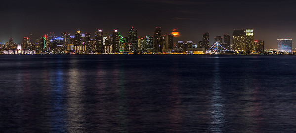Orange-colored Bull Moon rises among San Diego skyline