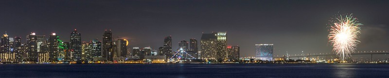 Rising moon, San Diego city skyline, fireworks, and Coronado Bridge