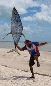 An artist dancing with a ghost-net fish sculpture