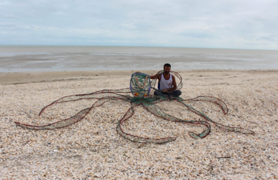 An artist poses with a ghost-net octopus sculpture