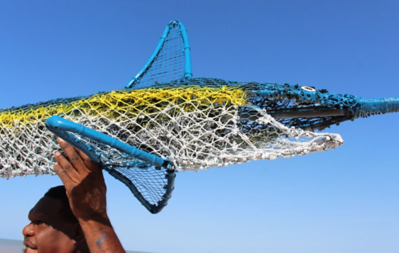 An artist hoists a ghost-net fish sculpture over his head