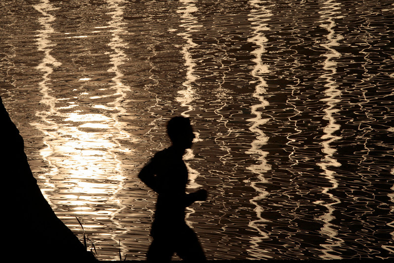Jogger in Silhouette and Reflection on Lake Merritt, Oakland CA