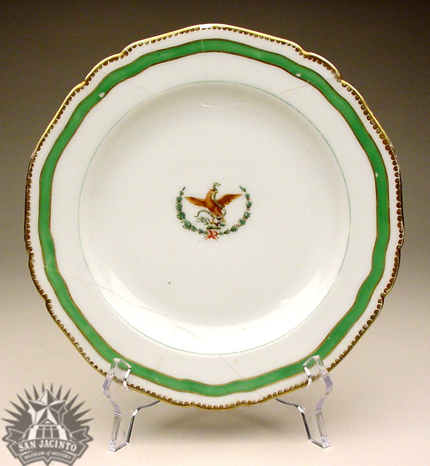 Handpainted china soup plate with Mexican eagle with snake on cactus in center framed by olive and laurel branch.  Formerly belonged to Antonio López de Santa Anna.  Bought by the donor from a Mexican family in Brownsville, Texas, who were refuges from the Diaz regime in Mexico and who had obtained the plate from Santa Anna.