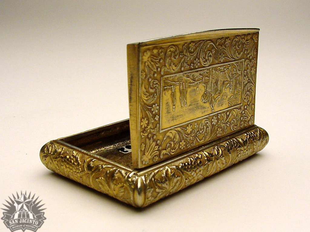 Gold plated snuffbox, said to have beloned to Antonio López de Santa Anna.  Hinged lid decorated with fruit and foliate design, with a central scene of a man on horseback talking to seated man, three men standing in the background.  Bottom has design with geometric shapes and animals.