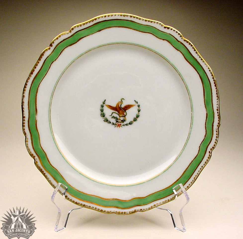 Handpainted china dinner plate with Mexican eagle with snake on cactus in center framed by olive and laurel branch.  Formerly belonged to Antonio López de Santa Anna.  Bought by the donor from a Mexican family in Brownsville, Texas, who were refuges from the Diaz regime in Mexico and who had obtained the plate from Santa Anna.