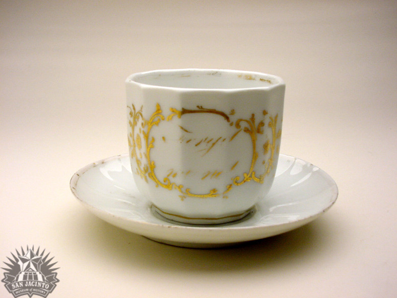 """White china saucer and cup that reads """"Forget me not"""", with a missing handle.  Given by Nancy Lea to Sam Houston, her son-in-law.  Family tradition holds that the gift was made as a peace offering after a clash of wills."""