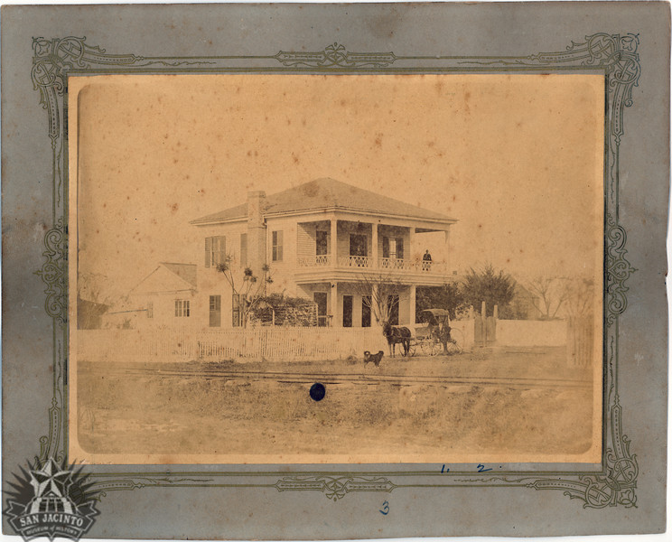 Residence at Orange, Texas, of R. B. Russell.  Two storey white house with 2nd level porch behind white fence, R. B. Russell and wife Lavinia on porch, man beside buggy pulled by one horse, with a dog.