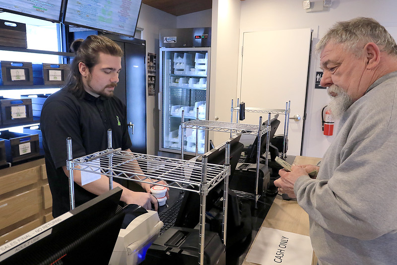 Sanctuary Medicinals in Gardner has been open for medical sales since November 23, 2018. On Wednesday March 6, 2019 they opened for recreational sales. Employee Brad Geslak checks out Ken Walker of Fitchburg their first recreational customer. SENTINEL & ENTERPRISE/JOHN LOVE