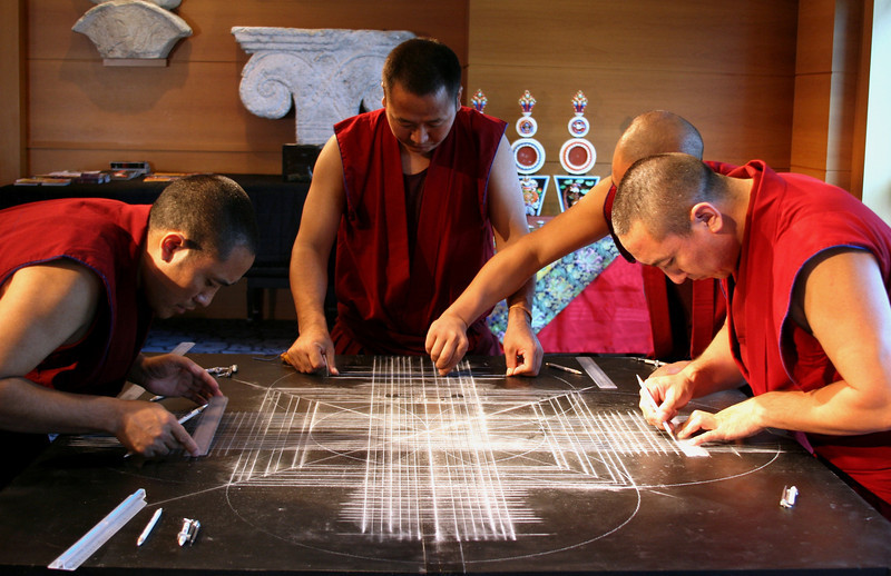 """2011 - On the first day, the monks devote several hours to draw an elaborate series of intersecting lines and connecting circles, to form the underlying design of the mandala.  They use a variety of familiar tools for this part of the process:  compass, ruler, pencil, string, chalk.<br /> <br /> Click on the link below for audio comments by Juana Clem McGhee.<br /> <a href=""""http://mesas.emory.edu/home/documents/audio/3JMcGhee.mp3"""">http://mesas.emory.edu/home/documents/audio/3JMcGhee.mp3</a>"""