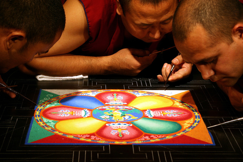 """2011 - In a coordinated effort, the monks move outward from the center, adding colors, patterns and symbols of the mandala.<br /> <br /> Click on the link below for audio comments by Myron McGhee.<br /> <a href=""""http://mesas.emory.edu/home/documents/audio/8MMcGhee.mp3"""">http://mesas.emory.edu/home/documents/audio/8MMcGhee.mp3</a>"""