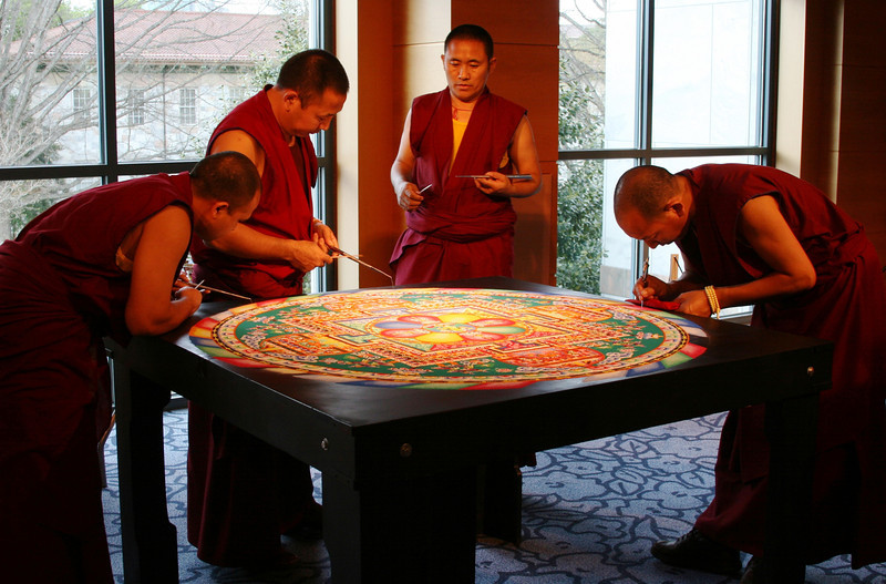 """2011 - On the final day of construction, the monks converge at the table to review their progress and complete the remaining design elements.<br /> <br /> Click on the link below for audio comments by Juana Clem McGhee.<br /> <a href=""""http://mesas.emory.edu/home/documents/audio/13JMcGhee.mp3"""">http://mesas.emory.edu/home/documents/audio/13JMcGhee.mp3</a>"""