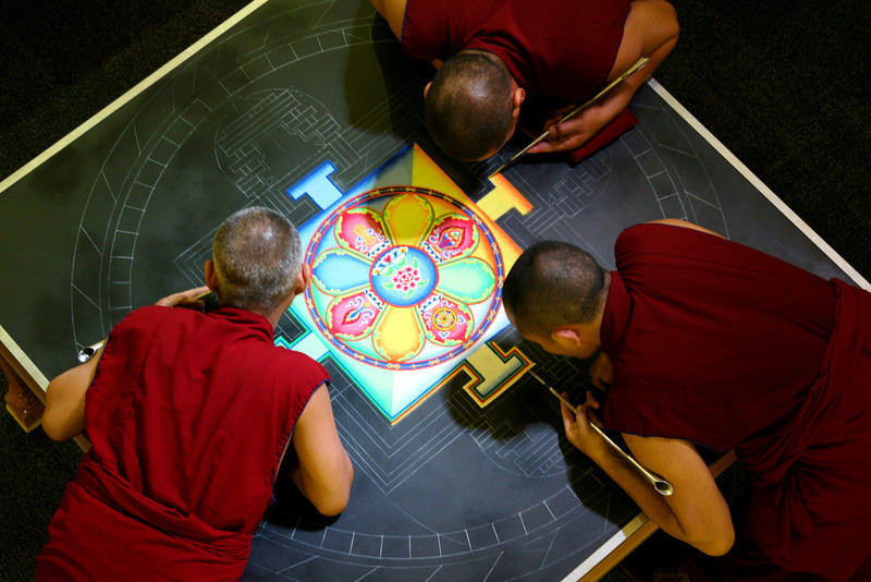 """2007 - The work involves standing and bending over the table for many hours each day.  This particular mandala, painted in 2007 during the visit of His Holiness the Dalai Lama, is centered around an image of the Buddha of Compassion (Avalokiteshvara).<br /> <br /> Click on the link below for audio comments by Tsepak Rigzin.<br /> <a href=""""http://mesas.emory.edu/home/documents/audio/9Rigzin.mp3"""">http://mesas.emory.edu/home/documents/audio/9Rigzin.mp3</a>"""