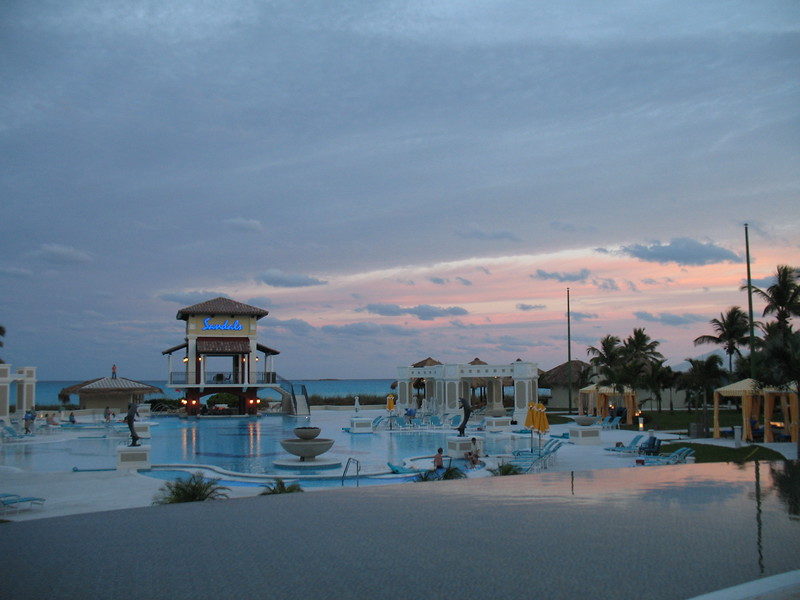 Sandals Emerald Bay - sunset over the pool and ocean.<br /> <br /> For more information on Sandals Emerald Bay or any of the other Sandals resorts, please contact us at Romance@SandnSunVacations.com