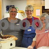 Victoria Boyd, Betty Nordstrom, and Marion Dencklau working together in the kitchen as Volunteers.