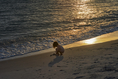 child plays in surf at sunset
