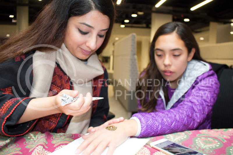 Zoona Jerral, master's student in architecture, eyed a smartphone image of a mehendi design to draw it for Frida Gonzales-Thurston, sixth-grader at Lee Elementary School and daugther of Sara Thurston, director of International Student and Scholar Services. Sara Thurston was the guest of honor for Sanskriti on Nov. 4, 2017. (Tiffany Roney | Collegian Media Group)