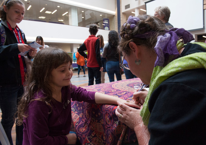 Lillian Cooper receives a henna tattoo from Ann Warren during the Sanskriti 2018 event at the Kansas State University Student Union on Nov. 3, 2018. Sanskriti is a Indian cultural inclusion event put on by Indian Students Association to promote learning about thier culture and traditions. (Photo by Justin Wright | Collegian Media Group)