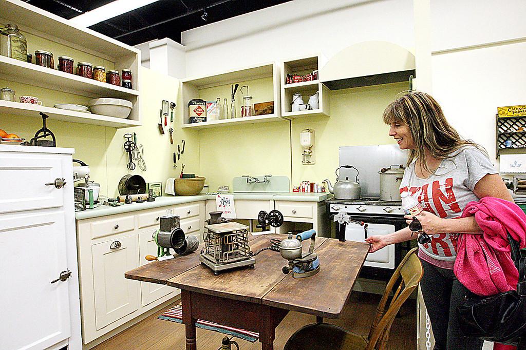 . Sylvia Vairo of Santa Cruz, looks in on a farm kitchen from more than 100 years ago at the Santa Cruz County Fair on Thursday. (Dan  Coyro -- Santa Cruz Sentinel)