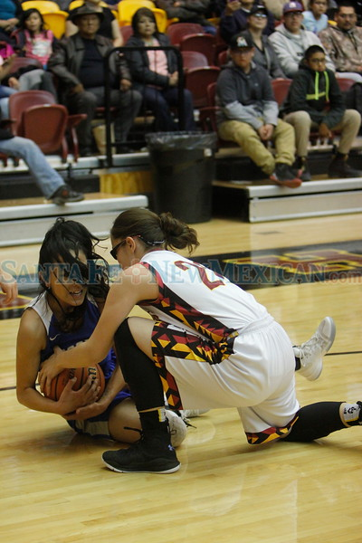 Socorro's Zoe Esquivel, number 14, and Santa Fe Indian's Cameron Conners, number 20, try to recover a loose ball during the first quarter of the Santa Fe Indian School vs Socorro High School at Santa Fe Indian School on Friday, Mar 2, 2018. Luis Sánchez Saturno/The New Mexican