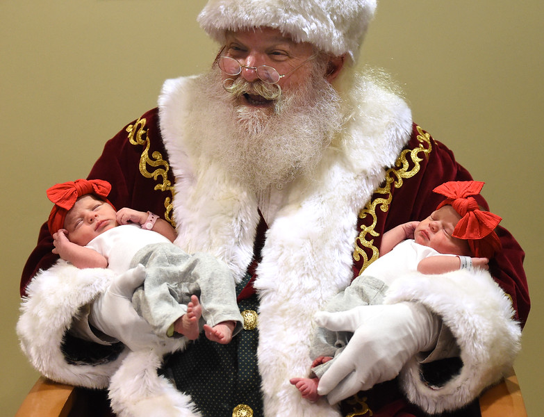 Santa Claus, portrayed by Moose Shattuck, has his hands full with twin newborns, Madelyn Borunda, left, and Macie Borunda, right, while visiting with babies in the birth center Wednesday, Dec. 12, 2018, at UCHealth Medical Center of the Rockies in Loveland.  (Photo by Jenny Sparks/Loveland Reporter-Herald)