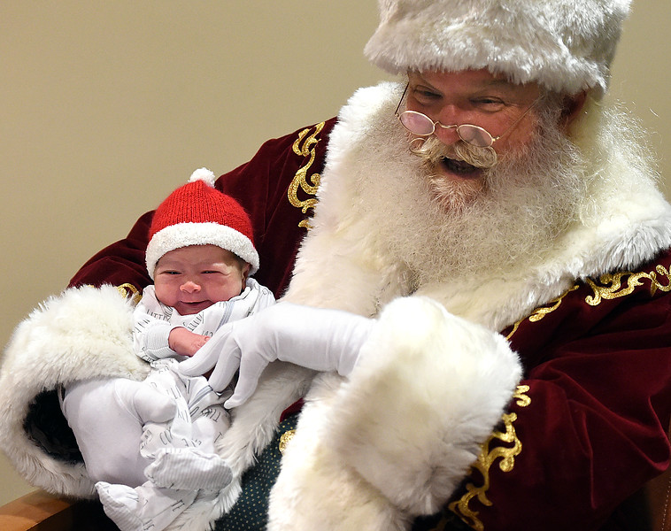 Newborn Jasper Klug flashes a quick smile as Santa Claus, portrayed by Moose Shattuck, holds him while visiting with babies in the birth center Wednesday, Dec. 12, 2018, at UCHealth Medical Center of the Rockies in Loveland.  (Photo by Jenny Sparks/Loveland Reporter-Herald)