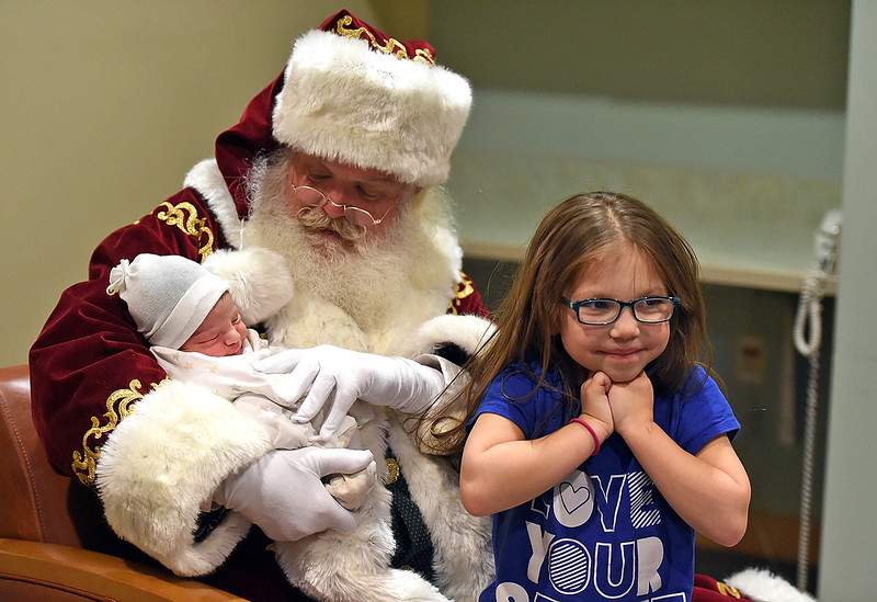 Big sister Inniaya Garza stands close by as Santa, portrayed by Moose Shattuck holds her newborn baby brother, Maximo Garza in the birth center Wednesday, Dec. 12, 2018, at UCHealth Medical Center of the Rockies in Loveland.  (Photo by Jenny Sparks/Loveland Reporter-Herald)