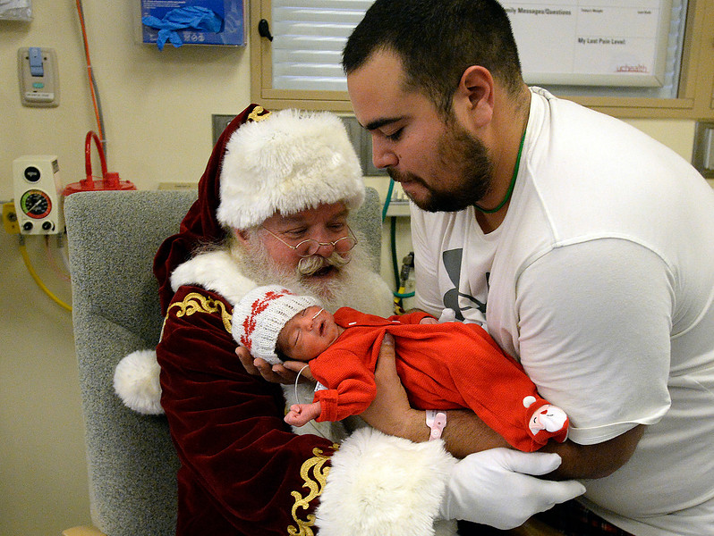 Esekiel Moran gently places his newborn daughter, Valentina Moran, in Santa's arms in the birth center Wednesday, Dec. 12, 2018, at UCHealth Medical Center of the Rockies in Loveland.  (Photo by Jenny Sparks/Loveland Reporter-Herald)