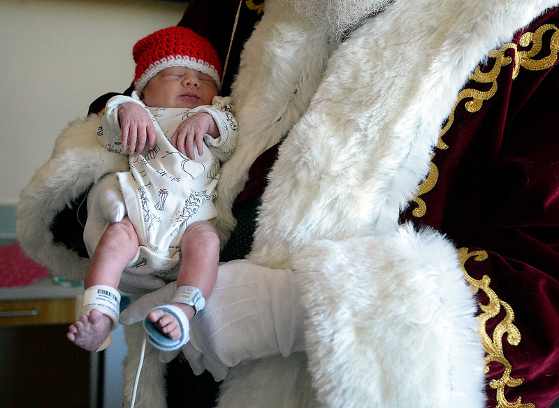 Newborn Riker Garrison, a patient in the Special Care Nursery at Medical Center of the Rockies, is held by Santa Claus Friday, Dec. 15, 2017, at the hospital in Loveland. Santa and Mrs. Claus visited the tiniest patients at the hospital in the Special Care Nursery.  (Photo by Jenny Sparks/Loveland Reporter-Herald)