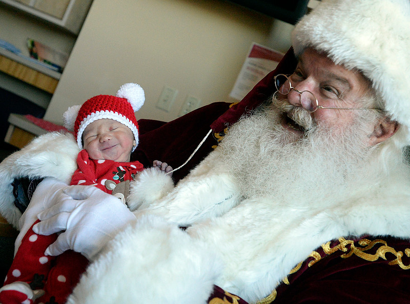 Santa Claus reacts as one day-old Natalia Zimmermann smiles as he holds her Friday, Dec. 15, 2017, at Medical Center of the Rockies in Loveland. Santa and Mrs. Claus visited the tiniest patients at the hospital in the Special Care Nursery.  (Photo by Jenny Sparks/Loveland Reporter-Herald)