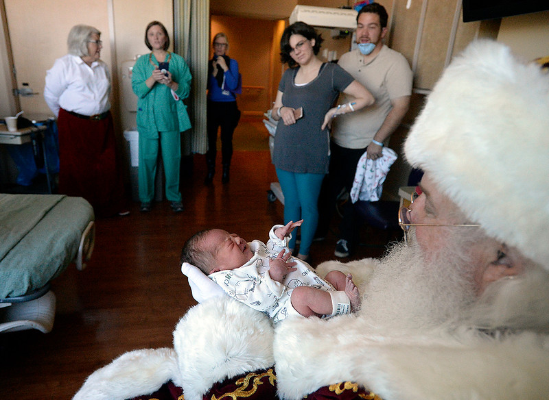 Newborn Riker Garrison, a patient in the Special Care Nursery at Medical Center of the Rockies, is held by Santa Claus Friday, Dec. 15, 2017, as his parents, family and hospital staff, and Mrs. Claus watch, at the hospital in Loveland. Santa and Mrs. Claus visited the tiniest patients at the hospital in the Special Care Nursery.  (Photo by Jenny Sparks/Loveland Reporter-Herald)