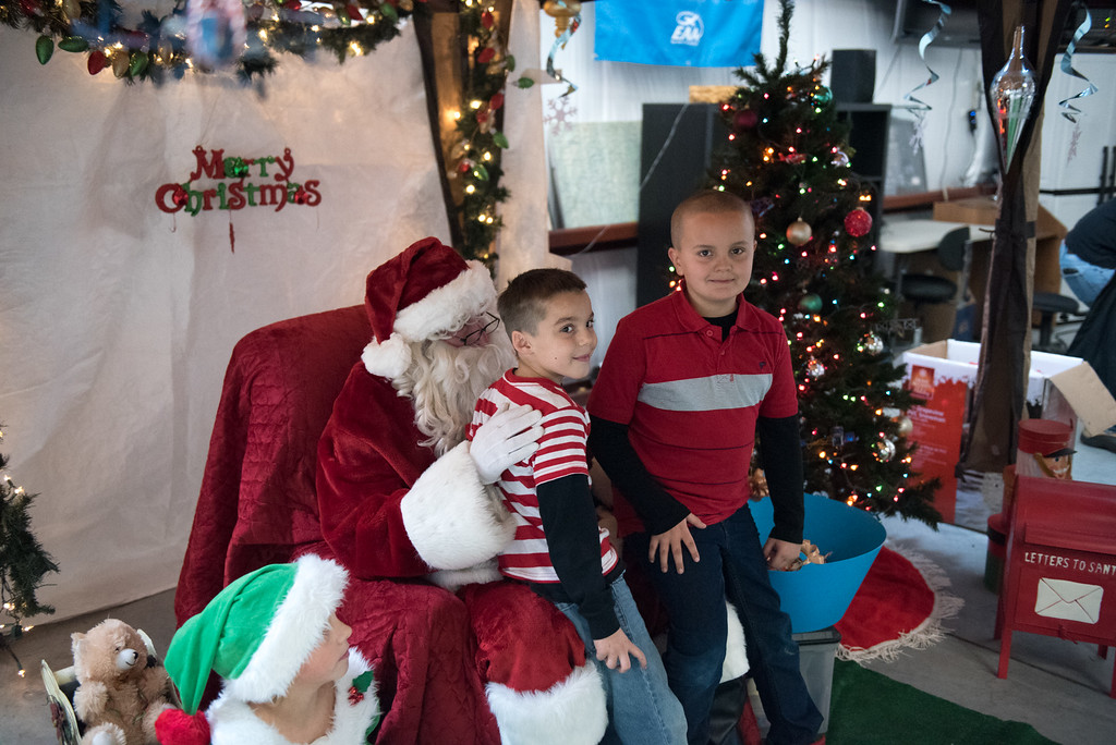 . 7 year old Hayden Alden (left) and Casiano Pedreza sit on Santa\'s lap at the Fitchburg Municipal Airport on Sunday Dec. 10, 2017.  SENTINEL & ENTERPRISE JEFF PORTER