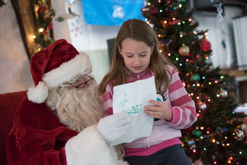 . 8 year old Taylor Green of Leominster reads off a list of items to Santa Claus at the Fitchburg Municipal Airport on Sunday Dec. 10, 2017.  SENTINEL & ENTERPRISE JEFF PORTER