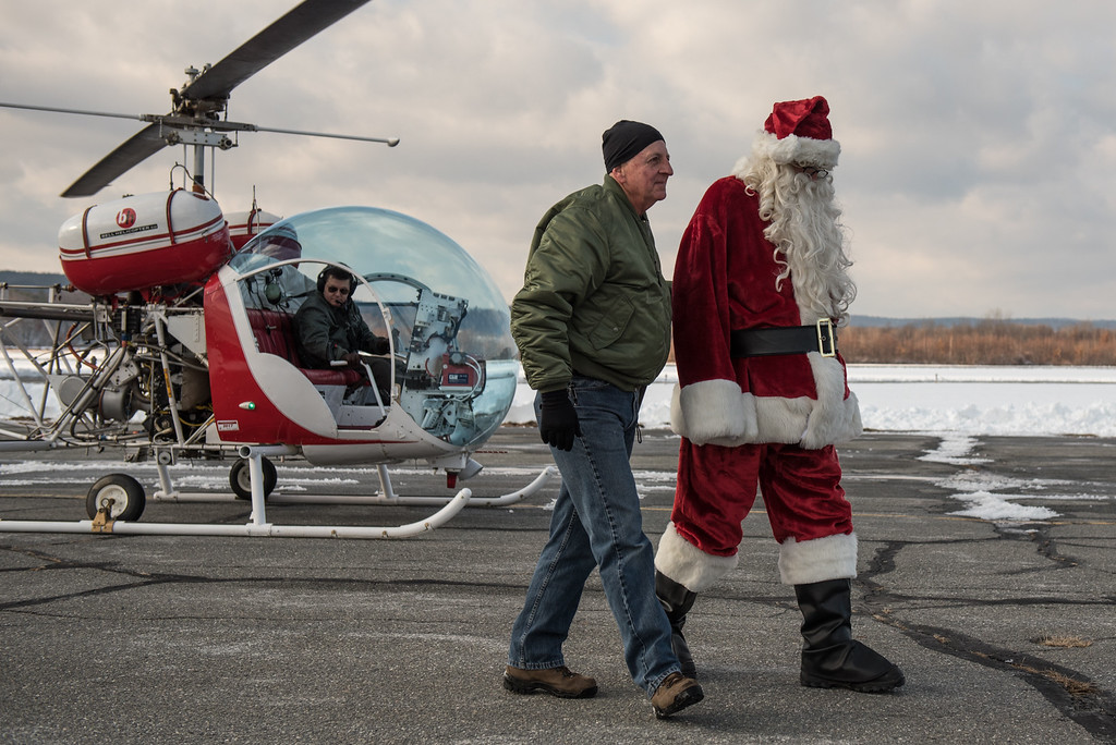 . Ground crew Dave Babineau (left) walks Santa Claus into the hanger after he lands at the Fitchburg Municipal Airport by helicopter on Sunday Dec. 10, 2017  SENTINEL & ENTERPRISE JEFF PORTER