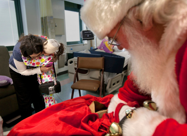 8 year old Hannah Matlaga gets a present from Santa. Santa Clause visited the Pediatrics department of Holy Name Medical Center in Teaneck to give presents to the children.<br /> Photo by Jeff Rhode / Holy Name Medical Center 12/18/13