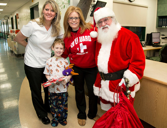 5 year old Johnny Alesso gets a present from Santa. Santa Clause visited the Pediatrics department of Holy Name Medical Center in Teaneck to give presents to the children.<br /> Photo by Jeff Rhode / Holy Name Medical Center 12/18/13