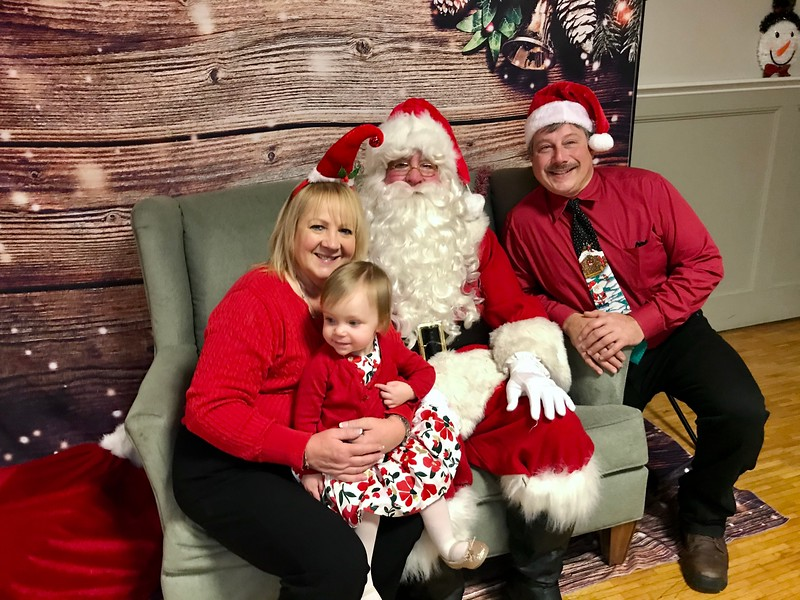 Claire Moore-Rosa, Mike Rosa and granddaughter Ashlan Farmer, 14 months, pose for a family photo with Santa. Photo by Mary Leach