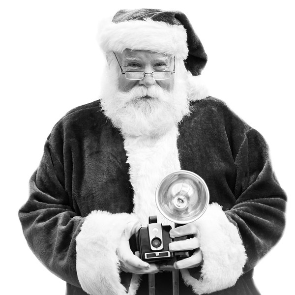 22081677 - an authentic santa claus holds an old vintage camera in black and white