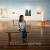 Tate Leone, a gallery assistant in the Strohl Art Center, sits in the 59th Chautauqua Annual Exhibition of Contemporary Art on June 23, 2016.