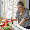 Annette Fisherman waters the flowers on her porch on Wednesday, June 12, 2019, as part of her preparation for the 2019 season. SARAH YENESEL/STAFF PHOTOGRAPHER
