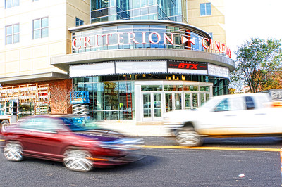 Cars on the move in front of the movies