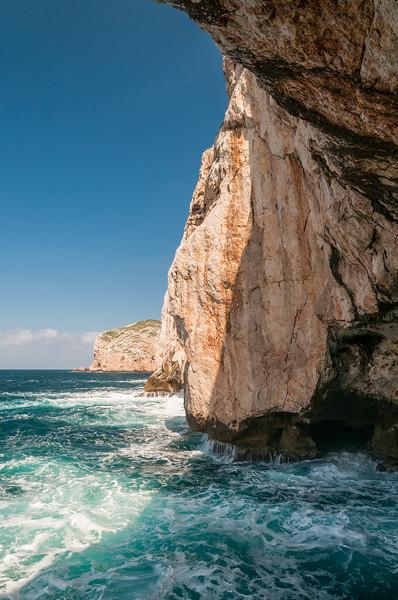 Alghero, faraglione del promontorio di Capo Caccia verso l'ingresso delle grotte di Nettuno.  Sullo sfondo, isola Foradada.