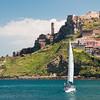 Sardinia, Italy: Castelsardo, panorama of the city. Sailing boat leaving the dock.