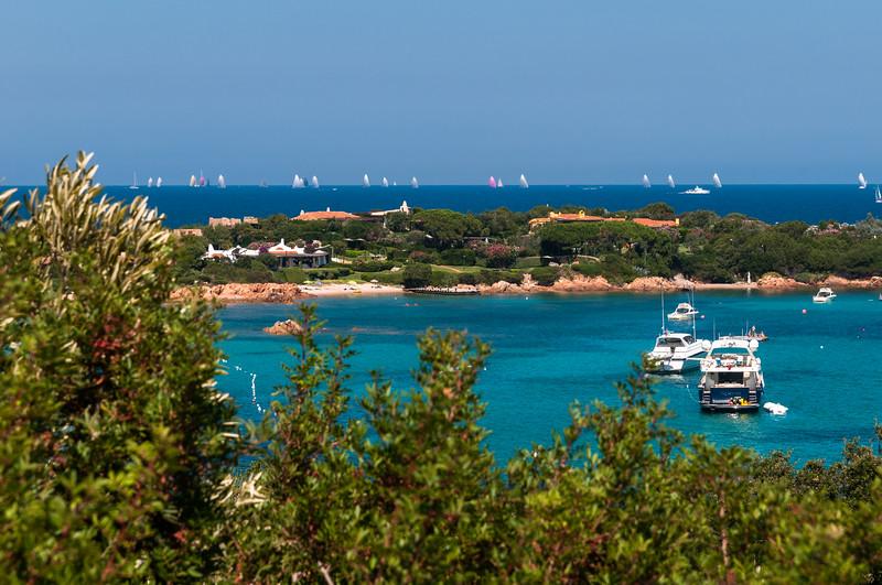 Costa Smeralda: barche ormeggiate sulla baia di Romazzino. Sullo sfondo si disputa una regata velica.