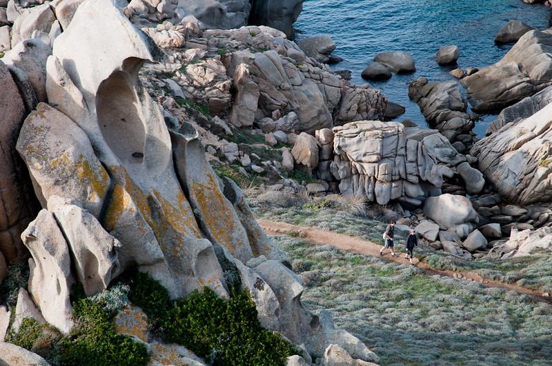 Sardinia, Italy: two people walking in Capo Testa bay at sunset  -  Sardegna: Santa Teresa Gallura, due persone camminano tra le rocce di  Capo Testa al tramonto
