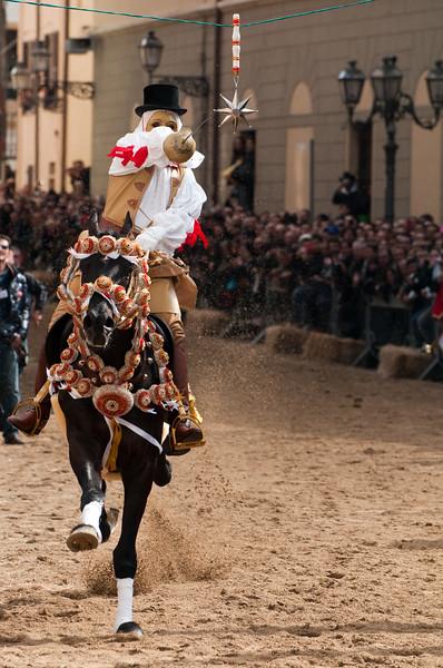 """Sardinia, Italy: Oristano, Sartiglia festival. A moment of the """"Palio della Stella"""" horse race. The """"Su Componidori"""", leader of the festival, tries to take the star with his sword. Un momento della Corsa alla Stella organizzata dal Gremio dei Contadini di San Giuseppe."""