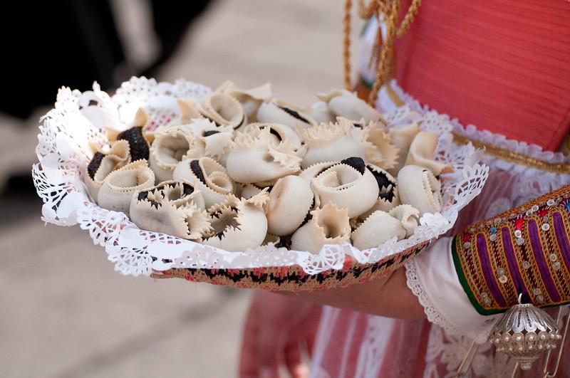 Sardinia, Italy: the Cavalcata Sarda Festival. Woman with a basket full of traditional sardinian desserts - Sardegna, Cavalcata Sarda di Sassari. Una donna con regge un cesto pieno di dolci tipici sardi.