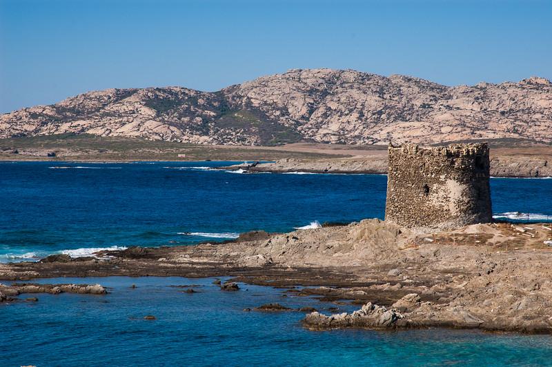 Stintino: spiagga e torre della Pelosa, nei pressi di Capo Falcone. Sullo Sfondo l'isola dell'Asinara,  sede dell'ex carcere di massima sicurezza.