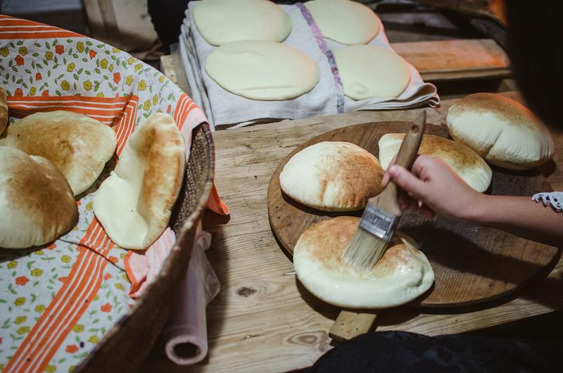 """Oliena (NU), Italy, 15.09.2013. Cortes Apertas. Preparazione del pane: """"Sa Panedda"""" di Oliena. Alla fine della cottura nel forno a legna, le panedde vengono pennellate con il latte."""