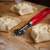 Preparazione di dolci sardi fatti in casa: casadinas, fatte con ripieno di ricotta o formaggio e uva passa.