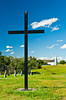 A large cross and the Church of St. Antoine de Padoue, in Batoche, Saskatchewan, Canada.